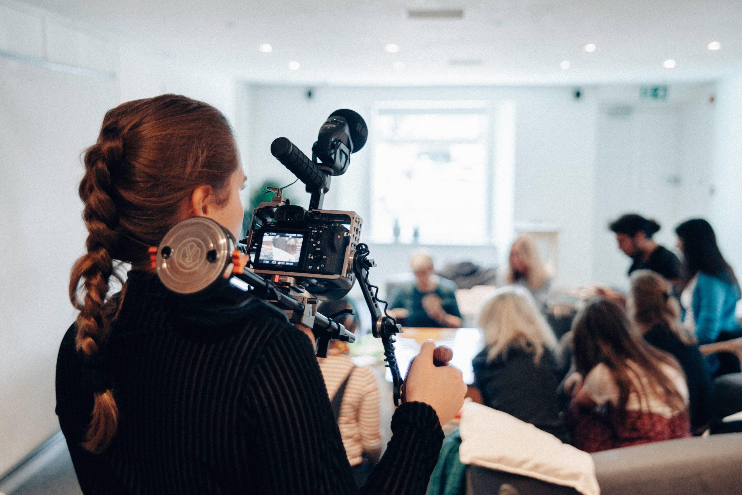 jeune femme derrière caméra devant salle de réunion avec personnes de dos